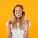 portrait-of-a-smiling-young-blonde-girl-pointing-RUWPEX6